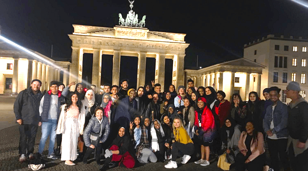 Students standing in front of the Brandenburg Gate at night