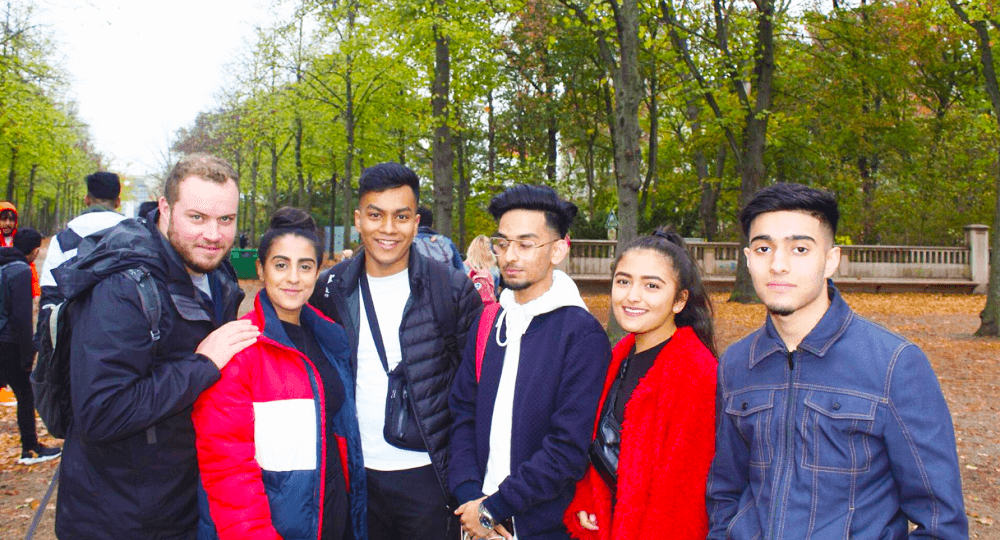 Students and teachers standing in a woodland area