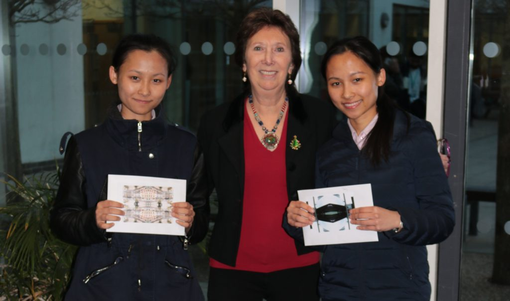 Identical twins standing with principal, holding their winning designs