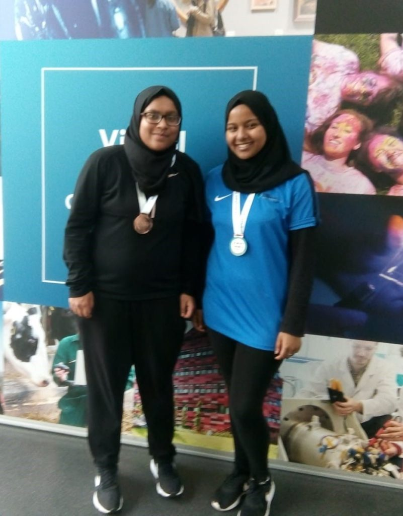 Two female students wearing hijabs and bronze medals