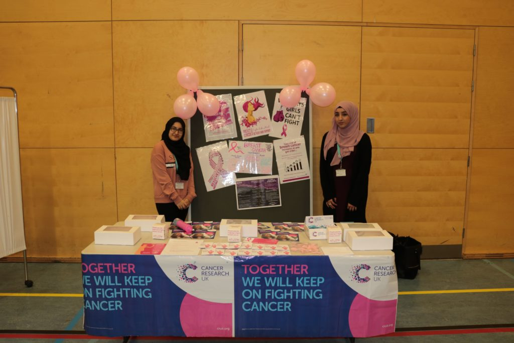 Photo of female students standing by a Cancer Research fundraising stall selling cupcakes