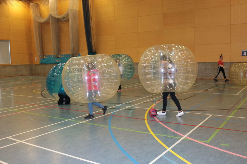 photograph of students inside large inflatable balls with their legs sticking out the bottom to play football
