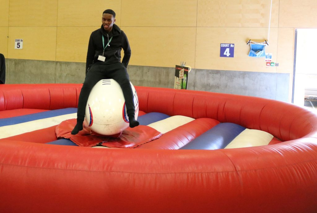 photo of male student straddling a mechanical rodeo inflatable bull